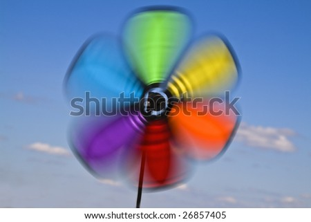 Colorful image of a vane in motion against a cloudy sky.