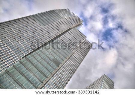 Colorful image of an isolated skyscraper on the background of the sky with some clouds - stock photo