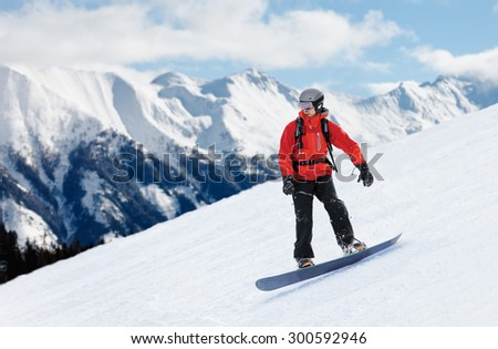 Colorful image of snowboarder in red jacket sliding down the slope - stock photo