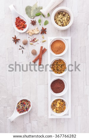 Colorful Indian spices. Assorted spices in ceramic dishes  on a desk. Overhead view with retro style processing. Natural light - stock photo