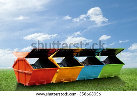Colorful Industrial Waste Bin (dumpster) for municipal waste or industrial waste on green grass and blue sky background,with ecology concept - stock photo