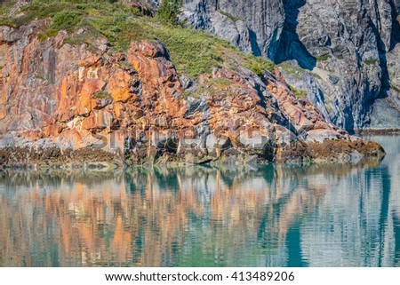 Colorful iron deposits of newly revealed cliffs previously covered by ice in Glacier Bay - stock photo