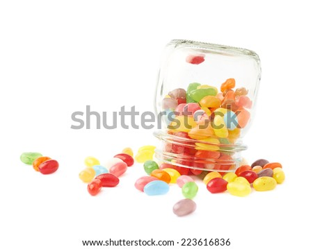 Colorful jelly bean candy sweets spilled out of a glass jar, composition isolated over the white background - stock photo