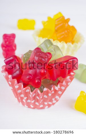 colorful jelly bears on light wooden background - stock photo