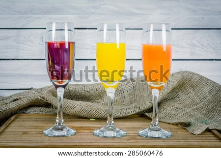 Colorful juice variations on a wooden table - stock photo