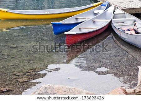 Colorful Kayaks beached on the edge of the Moraine Lake. - stock photo