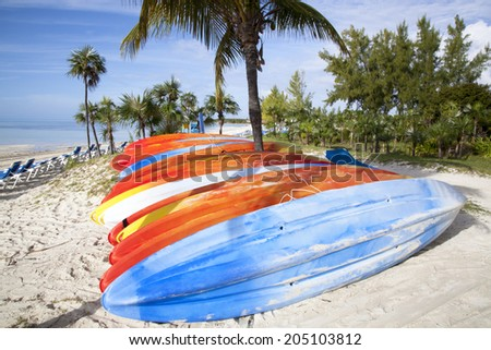 Colorful kayaks on a beach ready for action (Little Stirrup Cay, The Bahamas). - stock photo