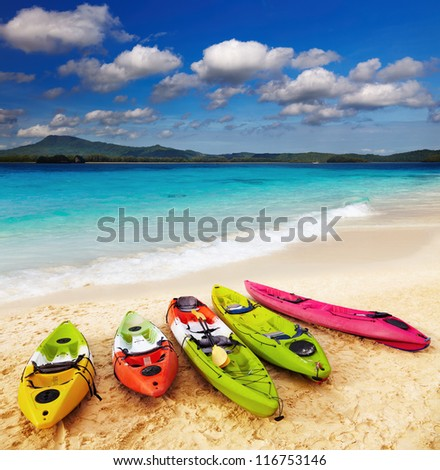 Colorful kayaks on the tropical beach - stock photo