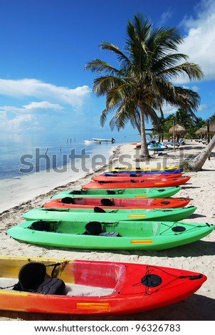 Colorful kayaks waiting for tourist on Mahahual resort town beach (Mexico).