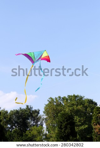 colorful kite flies high in the sky blue