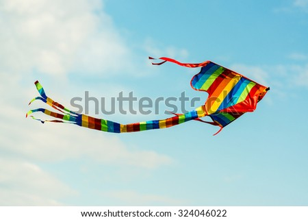 colorful kite flying in great blue sky - stock photo