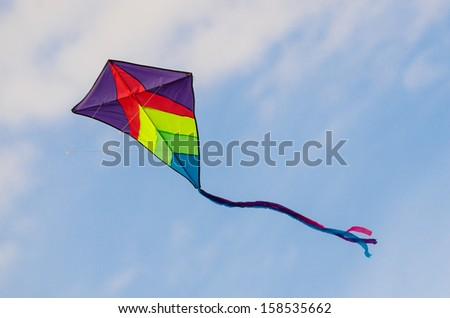 Colorful kite flying in the sky with clouds in background - stock photo
