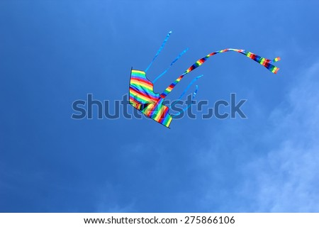 Colorful kite in the blue sky. - stock photo