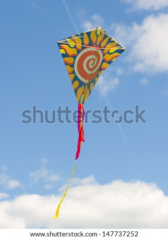 Colorful kite soaring against a blue sky. - stock photo