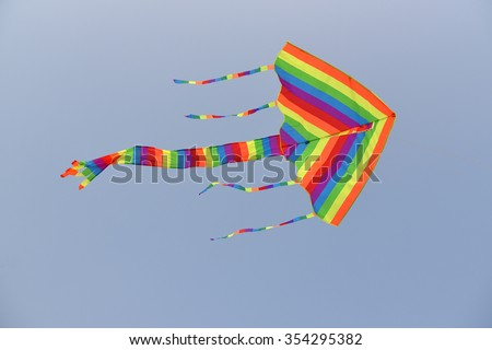Colorful Kite With long Tails Flying Against Clear Blue Sky