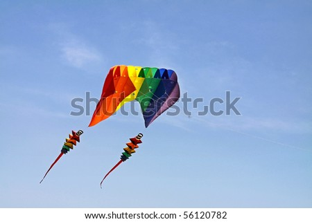 Colorful kite with two tails flying in the blue sky - stock photo