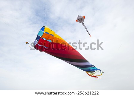 Colorful kites flying in a cloudy sky - stock photo