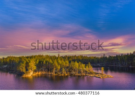 Colorful landscape with pines trees, calm lake and beautiful blue sky at sunset sunlight. Karelia Republic, Russia.