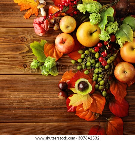 colorful leaves, apples and mushrooms on wooden background - stock photo