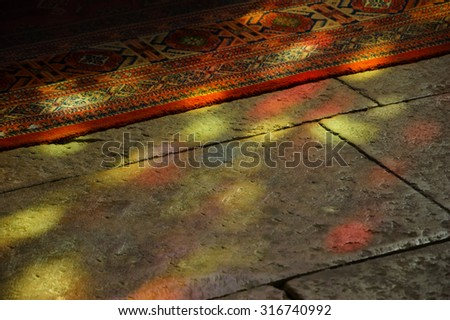 Colorful light spots on the the floor and carpet in church. Sunlight filtered through the stained glass window. A game of light and shadow. - stock photo