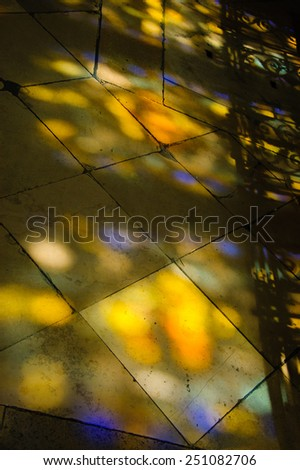 Colorful light spots on the tiled floor in the church and shadow of forging fence. Sunlight filtered through the stained glass window. - stock photo