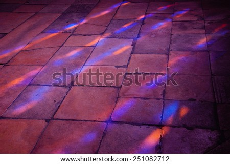 Colorful light spots on the tiled floor in the church. Sunlight filtered through the stained glass window. - stock photo