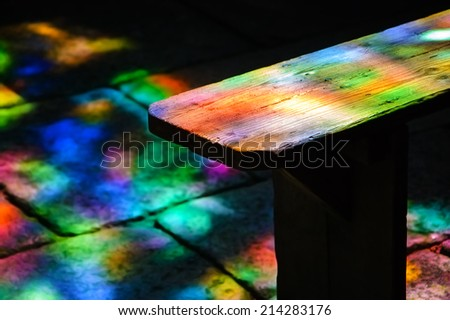 Colorful light spots on the wooden bench and stone brick floor in church. Sunlight filtered through the stained glass window. Selective focus on the bench. - stock photo