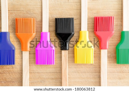 Colorful line of kitchen brushes in the colors of the rainbow for decorating and glazing pastries or basting meat arranged in an alternating pattern on a wooden background - stock photo