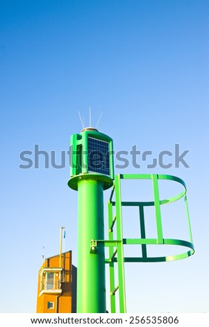 Colorful little lighthouse with staircase against a blue sky with copy space - stock photo