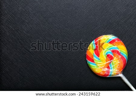 Colorful lollipop new with plastic packaging wrapped and white stick put on the black color leather background represent the sweet candy. - stock photo