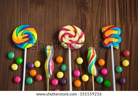 Colorful lollipops and candy drops on a wooden