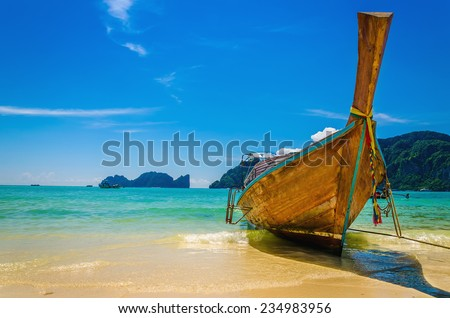 Colorful longtail boats at Maya Bay heavenly beach on a background of blue sky and azure sea and amazing limestone rocks, Phi Phi Islands, Thailand - stock photo