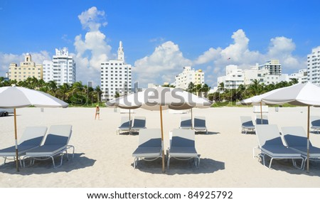 Colorful lounge chairs and umbrellas in popular South Beach in Miami. - stock photo