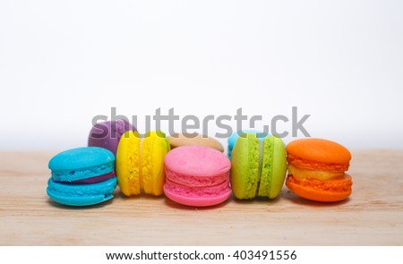 Colorful macaron cookies on wooden table background.