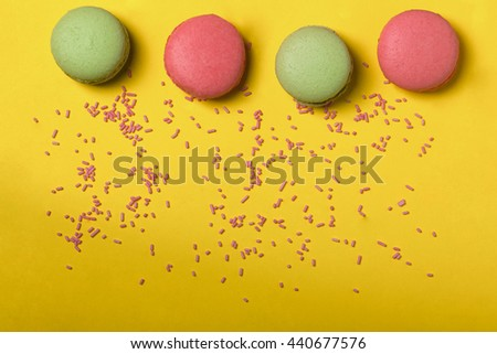 Colorful macaron pink and green color drop with many small dragee candies sprinkles on yellow background