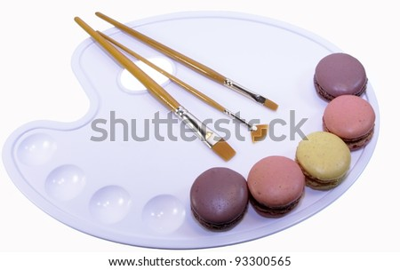 Colorful macarons and brushes on palette on white background