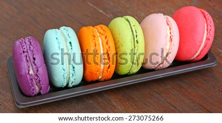 colorful macarons in a rows on the wood - stock photo