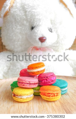 Colorful Macarons on Wooden Plate with Big Adorable White Teddy Bear Plush, Valentine's gift, Sweet and Romantic Concept - stock photo
