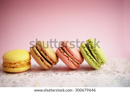 Colorful macaroons in a line on pink
