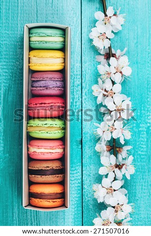 Colorful macaroons in paper box lying on turquoise wooden background - stock photo