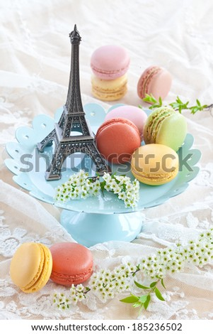 Colorful macaroons on blue plate and a little Eiffeltower - stock photo