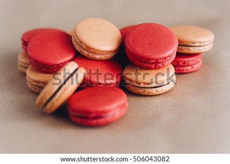 colorful macaroons stacked on craft background. space for text. catering at holidays. confection concept
