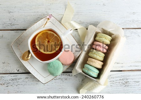 Colorful macaroons with cup of tea on color wooden  background - stock photo