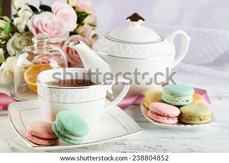 Colorful macaroons with cup of tea on color wooden table, on light background - stock photo