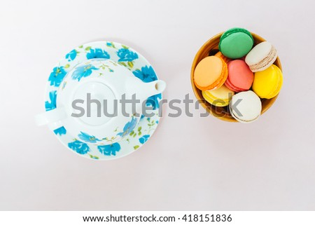 Colorful macaroons with cup of tea on pastel background