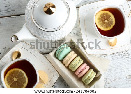 Colorful macaroons with teapot and cup of tea on color wooden  background - stock photo