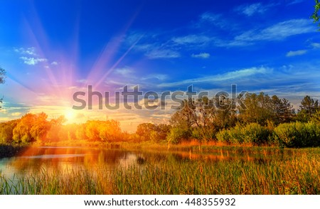 Colorful majestic sunset with a halo and of sunlight. picturesque scene. breathtaking scenery. Colorful summer sunrise over lake in forest. fantastic view. use as background. original creative images - stock photo