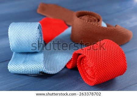 Colorful male ties on color wooden table background - stock photo