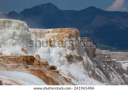 Colorful Mammoth Hot Springs cascading down a mountain side with steam rising and mountain landscape background at Yellowstone National Park. - stock photo