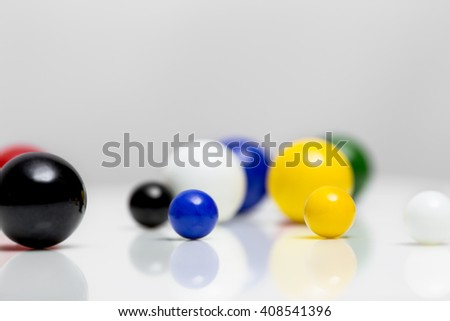 colorful marbles on white background with reflections - stock photo